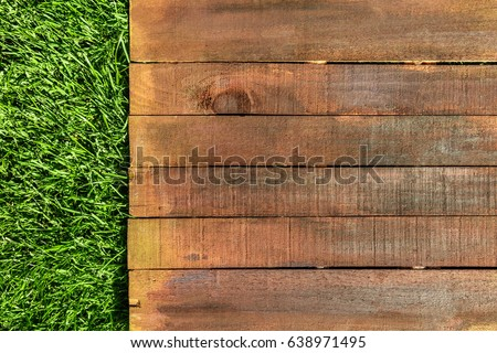A wooden board on green grass, a template for picnic-related design, overhead shot