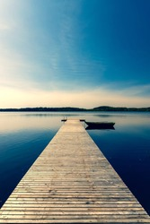 A wooden boat with oars moored to a pier on a lake in spring. The pier from the planks leaves with the prospect towards the horizon. The sun in the blue sky is approaching sunset. Latvia
