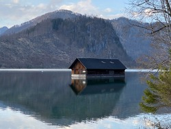 A wooden boathouse cabin in the mountain lake Almsee in Upper Austria