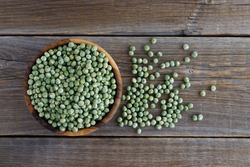 A wooden bowl full of dried green peas and peas scattered nearby on a wooden background.