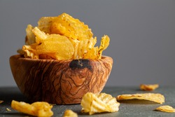 A wooden bowl of kettle cooked potato chips with crunchy ruffled texture. Some are spilt on the dark background. A moody pub, bar feeling or kitchen tabletop. Copy space for text to be added.