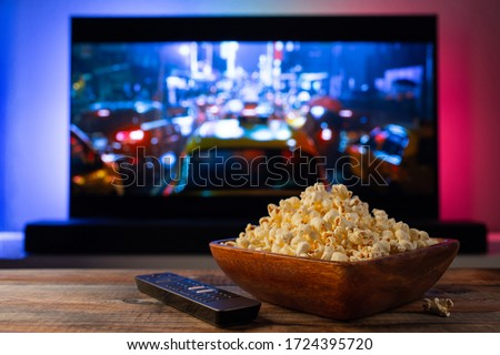 A wooden bowl of popcorn and remote control in the background the TV works. Evening cozy watching a movie or TV series at home