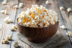 A wooden bowl of salted popcorn on rustic table.