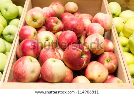 A wooden box of fresh apples on display at the farmers market