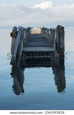 A wooden bridge in the middle of the water with its reflection #1365993818
