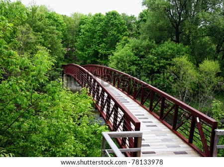 a wooden bridge leading into a forest
