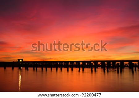 a wooden bridge over a river at sunrise