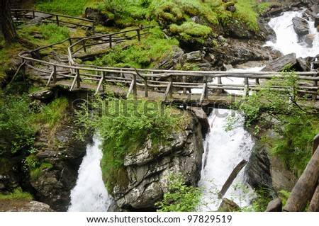 A wooden bridge over the so called Saent waterfalls, formed by the river Rabbies, in the Italian Dolomites