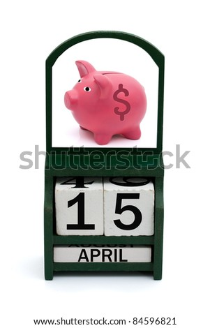 A wooden calendar with a date of April 15 and a piggy bank, Tax Day