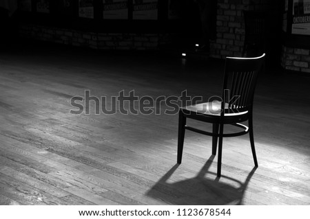 A wooden chair standing in the middle of an empty stage under the light of soffits, in black and white