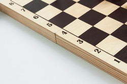 A wooden checkerboard in beige and black checkered with black numbers on the left edge is located diagonally on the right side of the image, on the left on a white background there is space for text