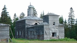 A wooden church in the summer on the edge of the forest.