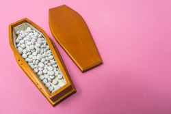 A wooden coffin full of gray round pills