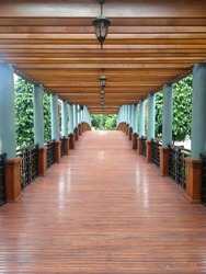 A wooden corridor of an outdoor area. Some unique lamps hanging on the roof's corridor. There are some  pillars on the corridor side. This make a symmetry view of the corridor.