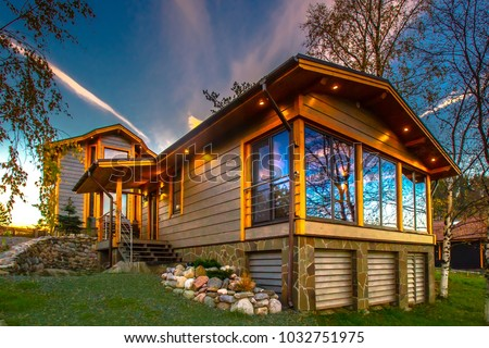 A wooden cottage with a green lawn. Cottage with panoramic windows. Glazing of cottages. Large windows in the house. Foto stock ©
