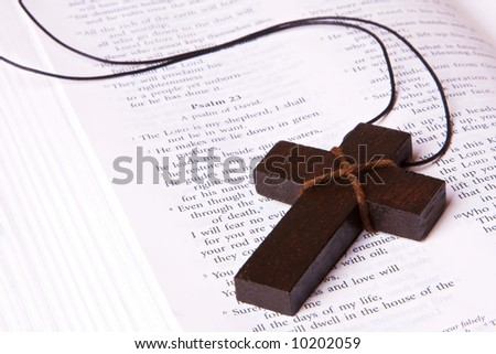 A wooden cross lying inside a bible, at Psalm 23. Can be used for any religious concept.