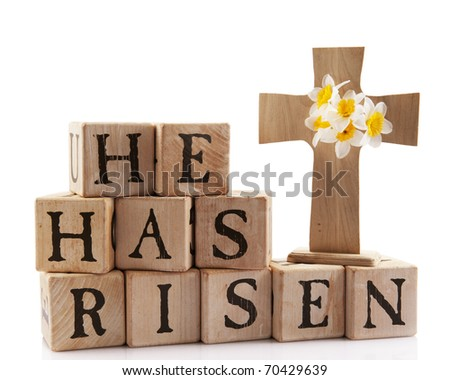 "A wooden cross with the words ""He has risen"" spelled out with rustic alphabet blocks.  Isolated on white. - stock photo"