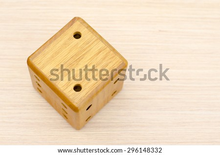 A wooden dice on a wooden table. The number fell to two