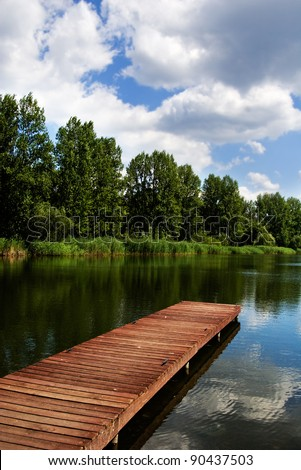 A wooden dock, pier, on a lake in summer sunny day, blue sky, white clouds, lake