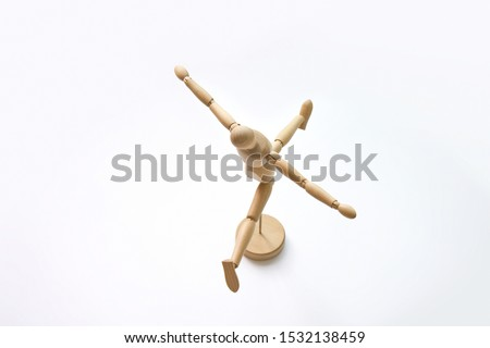 A wooden doll is dancing ballet doing splits and raising its hand up. Isolated on white background.