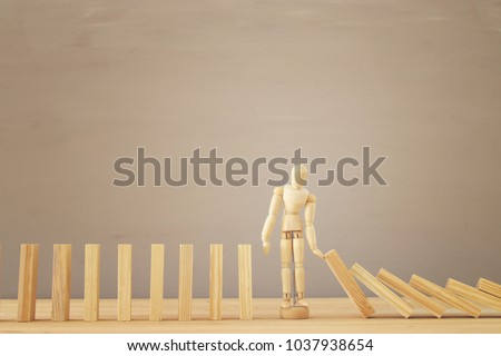 A wooden dummy stopping the domino effect. retro style image executive and risk control concept #1037938654