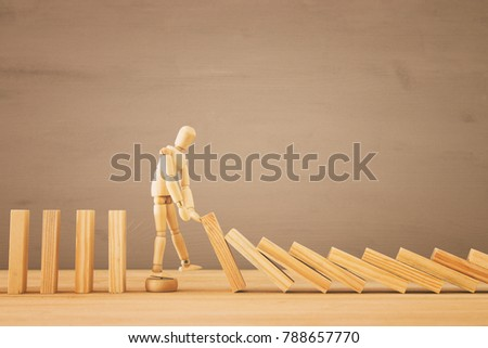 A wooden dummy stopping the domino effect. retro style image executive and risk control concept #788657770