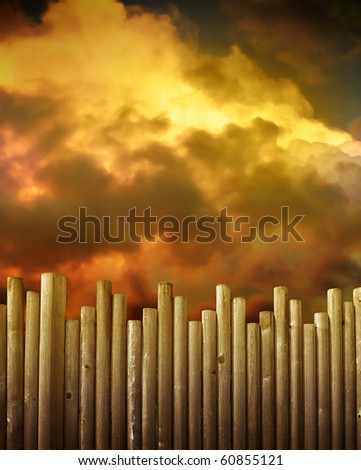 A wooden fence is in the foreground and red, gold and brown storm clouds are in the background. Use it to symbolize protection or a barrier concept.