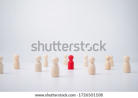 A wooden figure standing with a team to influence and empowerment. Concept of leadership, successful competition winner and Leader with influence and Social distancing for a new normal lifestyle