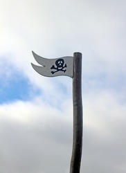A Wooden Flag with a Skull and Crossbones or Jolly Roger on flying against a cloudy blue sky
