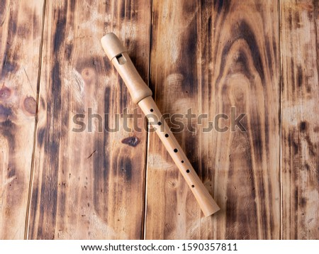 a wooden flute or recorder isolated on burnt wooden background, with copy space, musical education concept