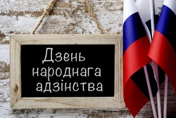 a wooden-framed chalkboard with the do you speak Russian? written in Russian, and some flags of Russia against a rustic wooden background