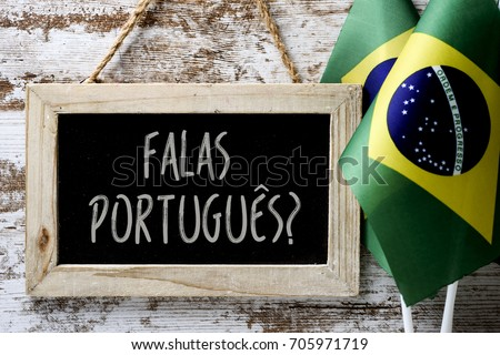 a wooden-framed chalkboard with the question falas portuges? do you speak Portuguese? written in Portugese, and some flags of Brazil against a rustic wooden background #705971719