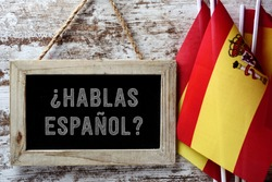 a wooden-framed chalkboard with the question hablas espanol? do you speak Spanish? written in Spanish, and some flags of Spain against a rustic wooden background