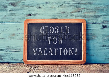 a wooden-framed chalkboard with the text closed for vacation written in it, on a rustic wooden surface, against a blue wooden background #466118252