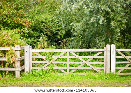 A wooden gate and fence in rural woodland