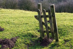 A wooden gate post isolated in the middle of a field where there were once walls or a fence separating fields