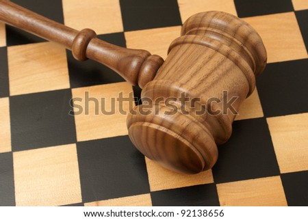 A wooden gavel and chess board represent strategy in legal situations.