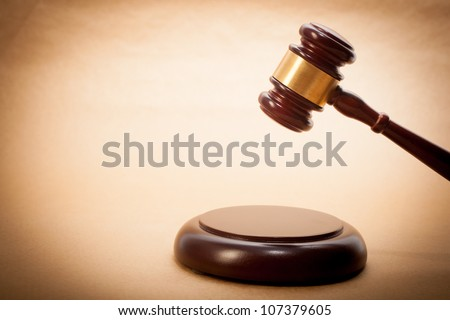 A wooden gavel and soundboard on a light brown background. - stock photo