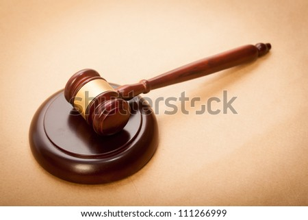 A wooden gavel and soundboard on a light brown background.