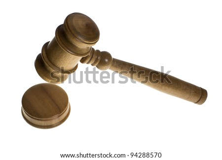 A wooden gavel is about to hit a strike plate isolated on white