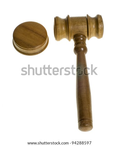 A wooden gavel rests beside a striker plate isolated on white