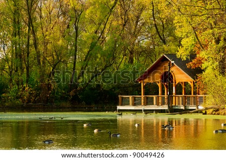 A Wooden Gazebo Over A Beautiful Blue Pond In Autumn Stock Photo ...