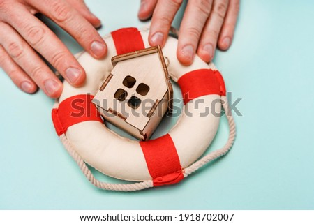 A wooden house lies in a lifeline. The concept of rental housing and assistance with the purchase of real estate Stockfoto ©