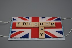 A wooden inscription, freedom day,above a flag of Great Britain and a face mask. Virus free concept