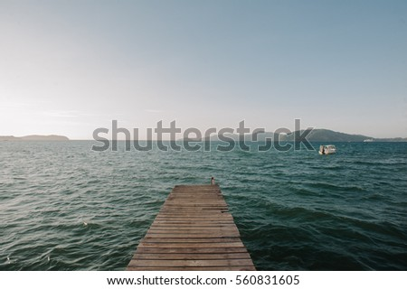 a wooden jetty facing sea with a boat and islands in front of it taken in Tanjung Aru, Sabah, Malaysia in 2016.