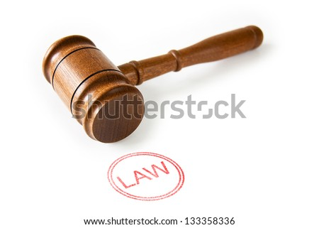 A wooden Judge's gavel with a red Law stamp against a white background