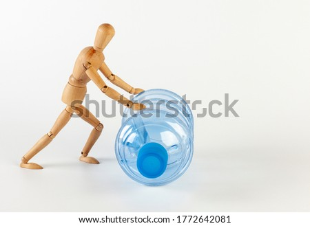 A wooden man rolls an empty five gallon plastic water bottle. Isolated on white on a white background.
