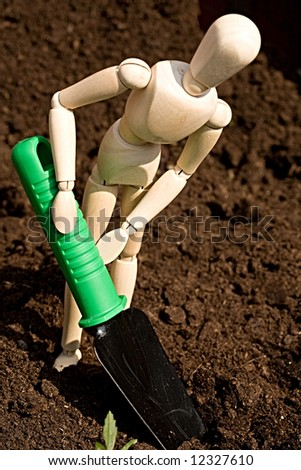 A wooden mannequin digging in the garden