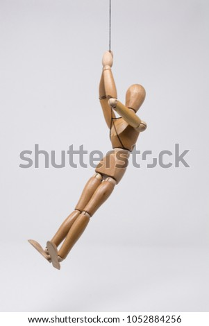 """A wooden mannequin hangs in the air. This image represents the expression, """"hanging by a thread"""" which describes being close to falling or failing or some other perilous situation. #1052884256"""