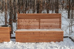 A wooden painted yellow color beautiful bench with white snow and a basket in a park in winter in a sunny day